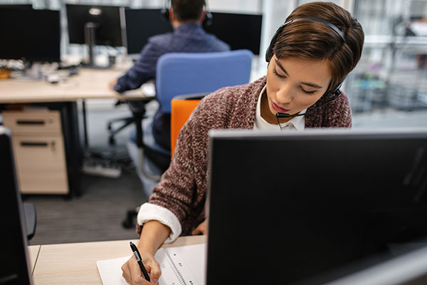 Worker with headset writing something down
