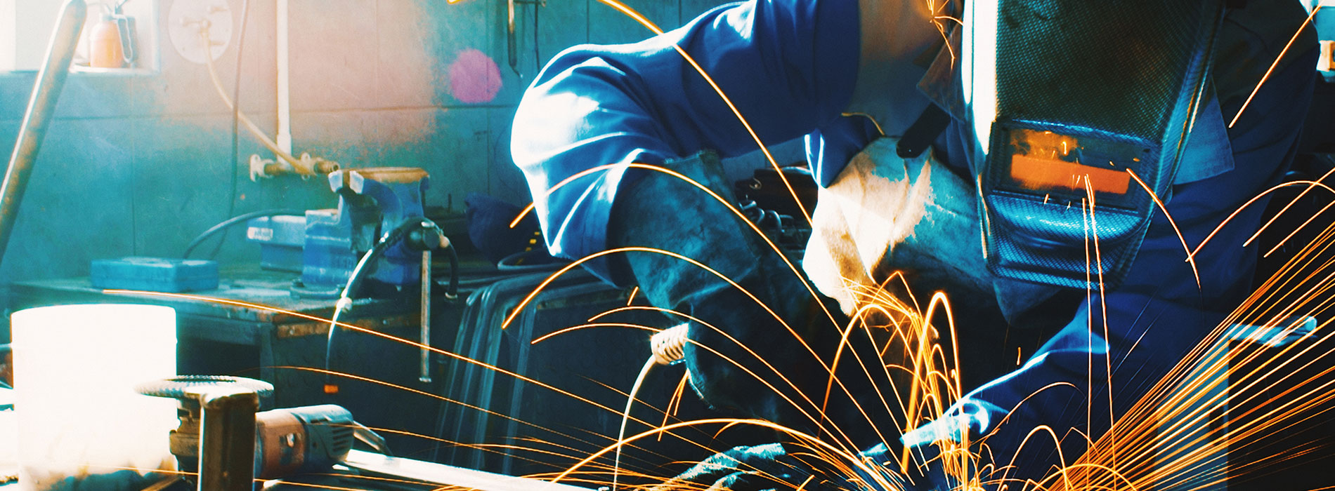 Worker in suit with sparks flying