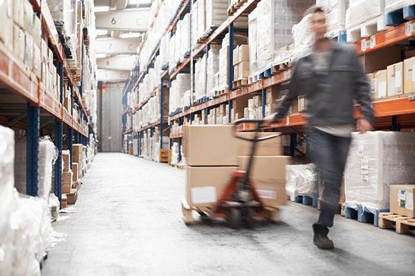 Worker drags cart through warehouse