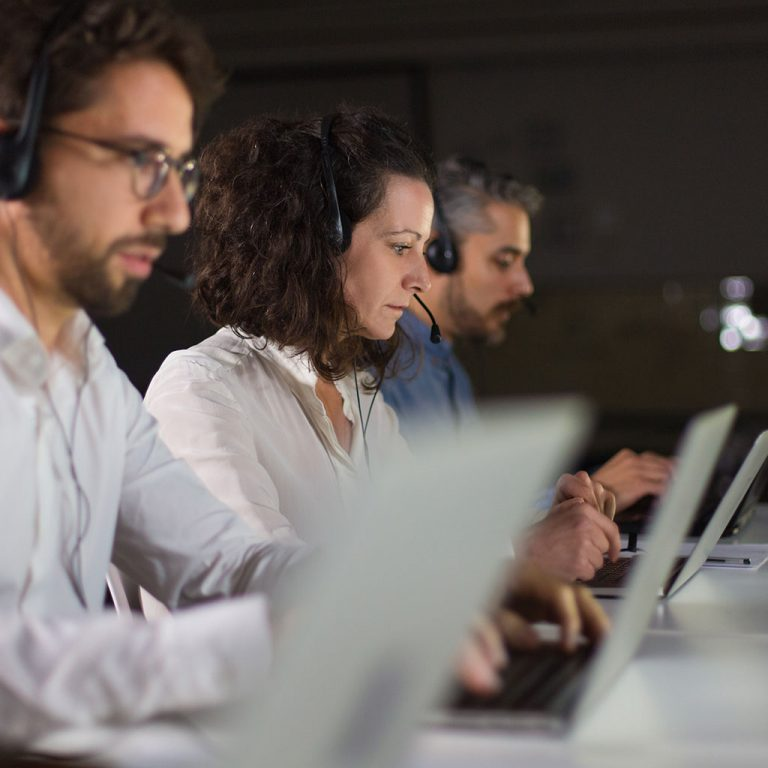 Workers with headsets on laptops