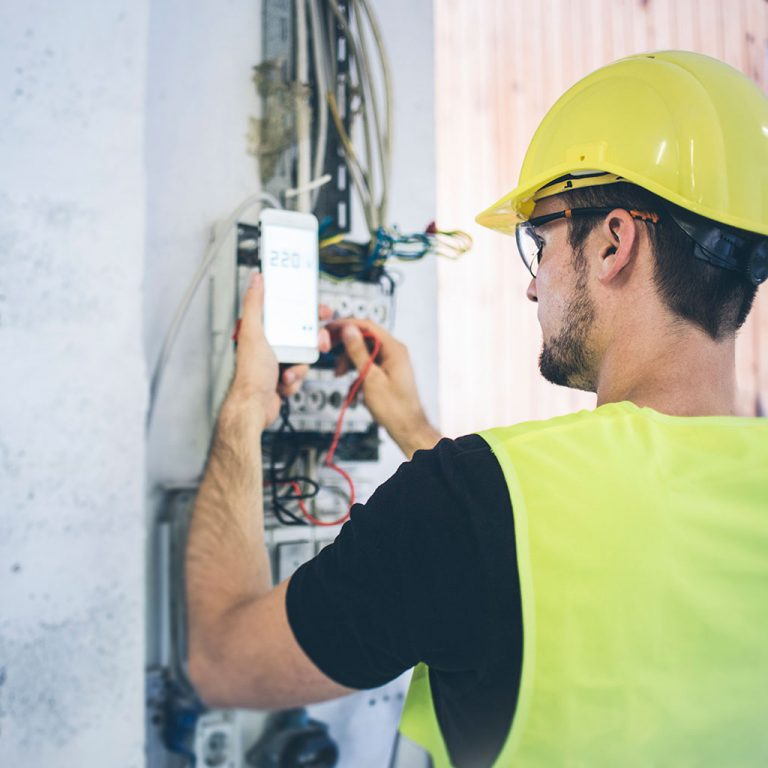 Worker in hard hat and hi-vis fixing wiring