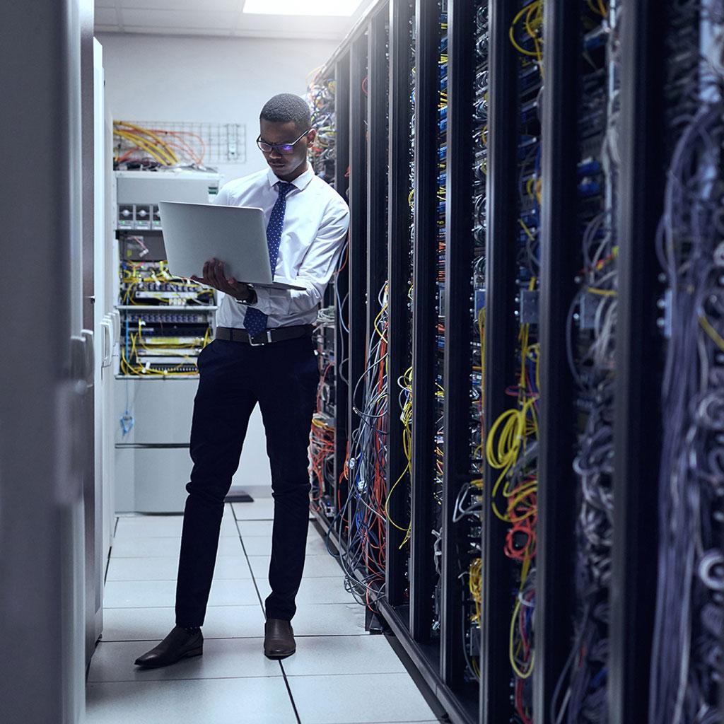 Man in server room on laptop