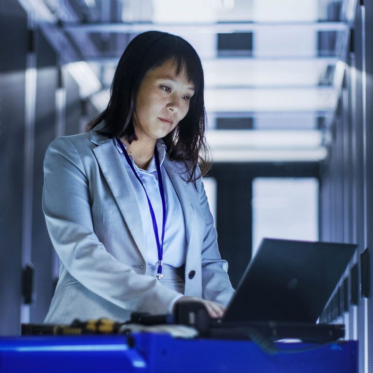 Woman on laptop in server room