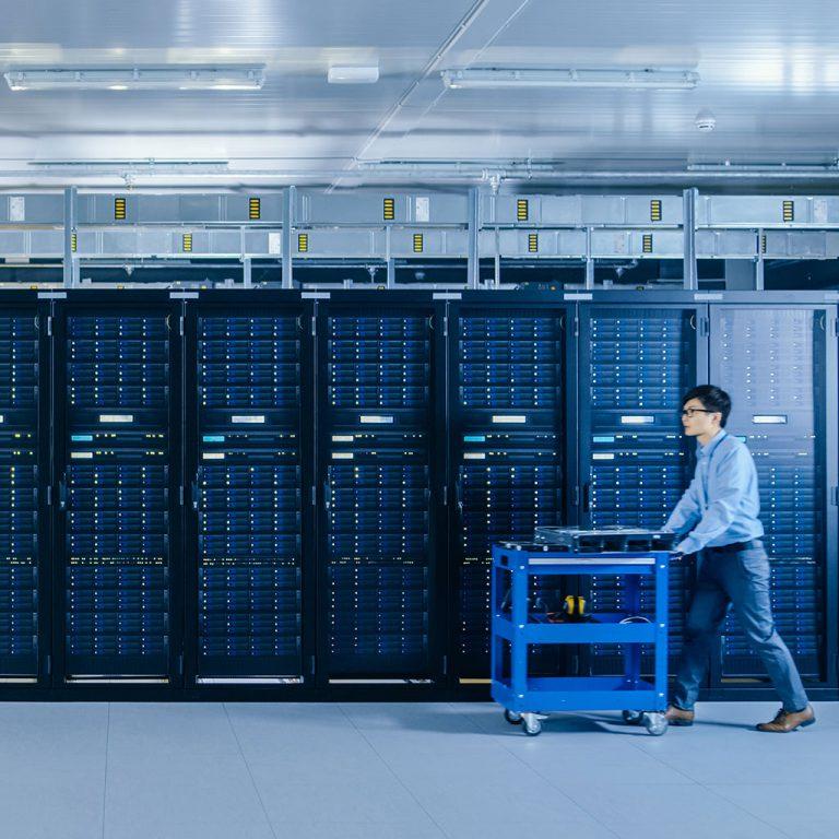 Man pushing cart through server room