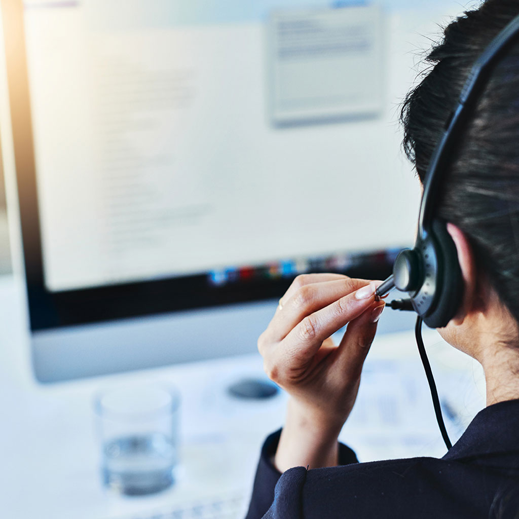 Worker with headset on monitor